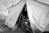 An eighty year old Syrian refugee who suffers from severe kidney problems attempts to leave her tent in Reyhanli refugee camp, Hatay, Turkey. There is little medical care for those in the refugee camps and only those suffering life threatening injuries are treated in Turkish hospitals when they arrive at the border. The small amount of nappies given to her are given to her ten year old grandchild who wets the bed because of his memories of Syria. 16th March 2012.