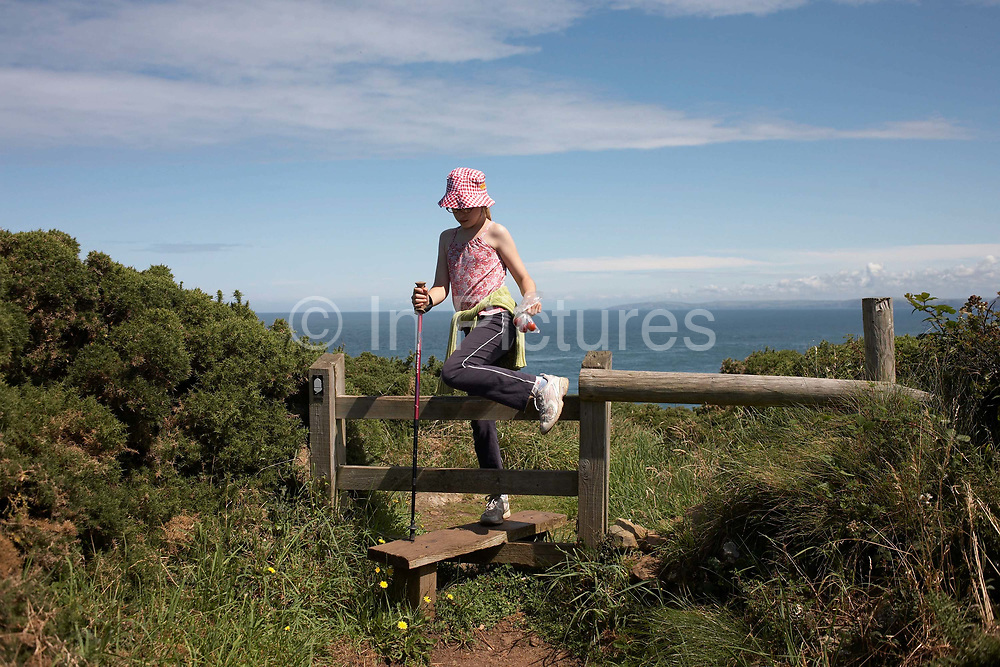 In fine, late-summer weather, an eleven year-old girl gingerly steps over a stile on the coastal path at Carregwastad Point, near Strumble Head, Pembrokeshire, Wales. Steadying herself with a walking pole, she climbs over wearing trainers rather than stout walking boots as this path is gentle for younger outdoor enthusiasts. The Pembrokeshire Coast Path is the first National Trail in Wales. Opened in 1970, the path is almost entirely contained within the boundaries of the Pembrokeshire Coast National Park that takes in 17 Sites of Scientific Interest (SSSI), two nature reserves, and Wales' only marine nature reserve. The cliff tops offer wonderful expanses of wildflowers in Spring (April and May are best). Wide variety of birds nest along the cliffs, and grey seals can often be seen in the water below.