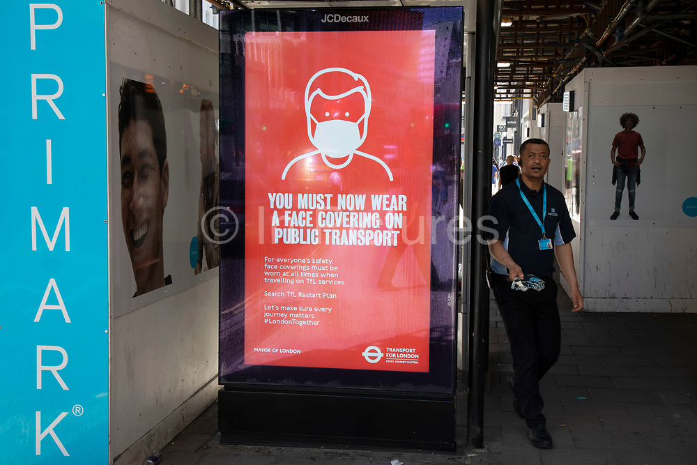 HM Government, Public Health England, NHS advertising boards advice wear a face covering or face mask while travelling on public transport as the Coronavirus lockdown measures are set to ease further, the west end starts to fill with people as they return to the shopping district on Oxford Street and the quiet city starts coming to an end on 22nd June 2020 in London, England, United Kingdom. As of today the government has relaxed its lockdown rules, and is allowing some non-essential shops to open with individual shops setting up social distancing queueing systems.