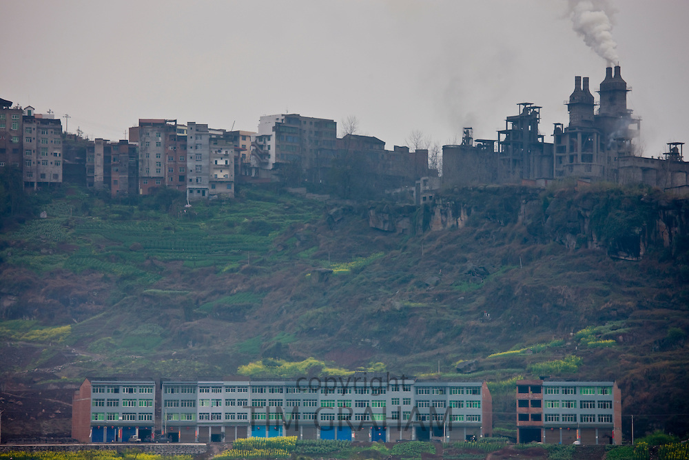 Houses in the shadow of a cement factory, beside the Yangtze River, China