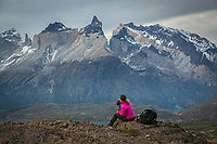 A lone female hiker takes in the epic views of Torres del Paine National Park, Chile