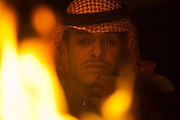A Bedouin man looks out over the flames of a fire at a camp in the desert in Wadi Rum, Jordan.