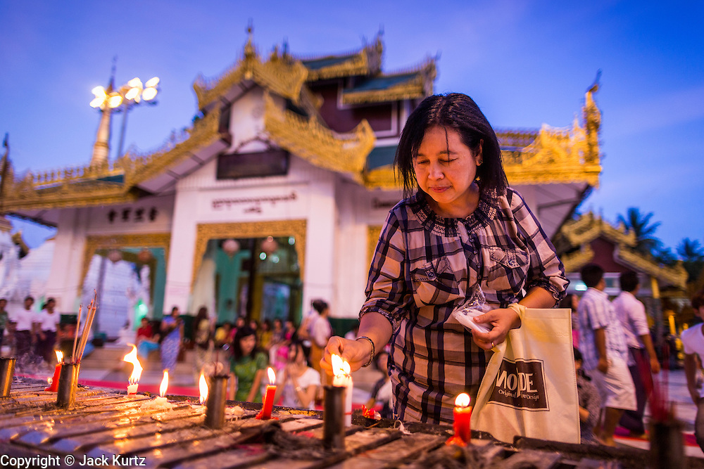15 JUNE 2013 - YANGON, MYANMAR: A woman makes merit and prays with candles at Shwedagon Pagoda. Shwedagon Pagoda is officially known as Shwedagon Zedi Daw and is also called the Great Dagon Pagoda or the Golden Pagoda. It is a 99 meter (325ft) tall pagoda and stupa located in Yangon, Burma. The pagoda lies to the west of on Singuttara Hill, and dominates the skyline of the city. It is the most sacred Buddhist pagoda in Myanmar and contains relics of the past four Buddhas enshrined: the staff of Kakusandha, the water filter of Koṇāgamana, a piece of the robe of Kassapa and eight strands of hair from Gautama, the historical Buddha. Burmese believe the pagoda was established as early ca 540BC, but archaeological suggests it was built between the 6th and 10th centuries. The pagoda has been renovated numerous times through the centuries. Millions of Burmese and tens of thousands of tourists visit the pagoda every year, which is the most visited site in Yangon.  PHOTO BY JACK KURTZ