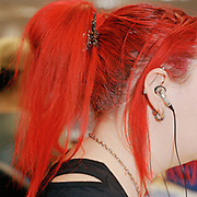 Sue Williams, out bound call centre agent demonstrates her individuality in the colour of her red hair while making calls from her office desk in London, United Kingdom. Office workers have little opportunity to express themselves because of the constraints of the office dress code. From Desk Job, a project which explores office life around the World.