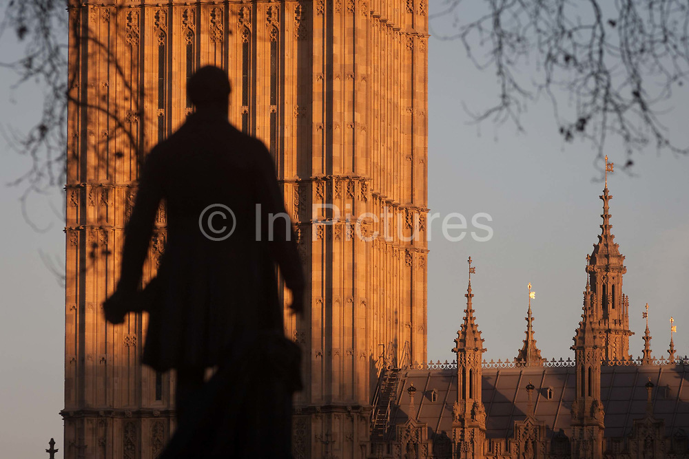 The silhouetted statue of Sir Robert Peel and the Elizabeth Tower of the British parliament, on 17th January 2017, in London England. The Elizabeth Tower previously called the Clock Tower named in tribute to Queen Elizabeth II in her Diamond Jubilee year – was raised as a part of Charles Barrys design for a new palace, after the old Palace of Westminster was largely destroyed by fire on the night of 16 October 1834. The new Parliament was built in a Neo-gothic style, completed in 1858 and is one of the most prominent symbols of both London and England. Sir Robert Peel, was a British statesman and member of the Conservative Party, served twice as Prime Minister of the United Kingdom and twice as Home Secretary. He created the modern police force and officers known as bobbies and peelers.