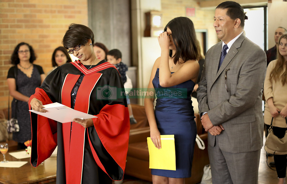 May 9, 2017 - Toronto, Ontario, Canada - TORONTO, ON - MAY, 9    Veigas looks at her degree as her daughter Jadyn 15 and husband Joseph D'Souza..Despite being diagnosed with terminal cancer, Precilla Veigas fulfilled a lifelong dream of earning her PhD in medical science. Because her prognosis is uncertain, she received the degree at a special convocation ceremony arranged just for her, and her family, at U of T on Tuesday..May 9, 2017 Richard Lautens/Toronto Star Richard Lautens/Toronto Star (Credit Image: © Richard Lautens/The Toronto Star via ZUMA Wire)