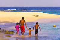 Family walking on the beach on Pelican Island (a.k.a. Icotupo Island), San Blas Islands (Kuna Yala), Caribbean Sea, Panama