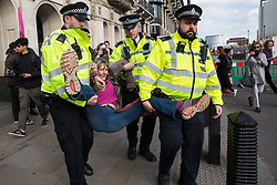 London, UK. 8 October, 2019. Metropolitan Police officers arrest a climate activist from Extinction Rebellion who had blocked Whitehall on the second day of International Rebellion protests to demand a government declaration of a climate and ecological emergency, a commitment to halting biodiversity loss and net zero carbon emissions by 2025 and for the government to create and be led by the decisions of a Citizens' Assembly on climate and ecological justice.