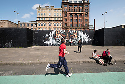 Street scene with street art on walkway beside River Clyde in central Glasgow , Scotland, United Kingdom