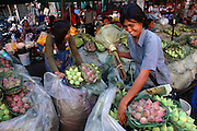 Vendor prepares lotus flowers for sale at Pak Klong Talat Market, Bangkok, Thailand