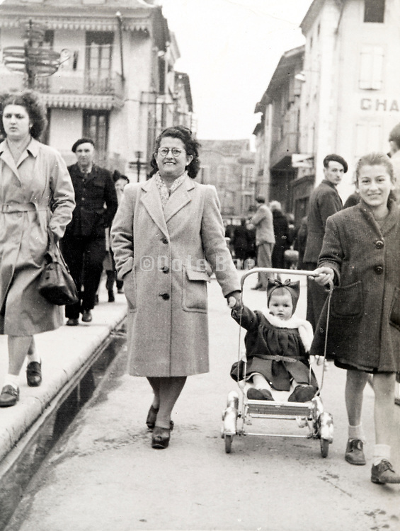 mother walking with daughter and toddler in a stroller France ca 1950s