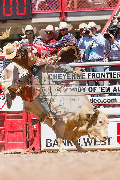 Bull rider Caleb Sanderson is tossed from his ride during the Bull Riding finals at the Cheyenne Frontier Days rodeo in Frontier Park Arena July 26, 2015 in Cheyenne, Wyoming. Frontier Days celebrates the cowboy traditions of the west with a rodeo, parade and fair.