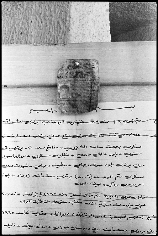 An identification card found in the mass grave near  Al-Musayab, Iraq, pinned up outside the gymnasium of the local sports center, now the home of an Iraqi human rights organization which is overseeing the exhumations of bodies from local mass graves. People come from all over to check the clothing and ID cards of the bodies, looking for relatives.