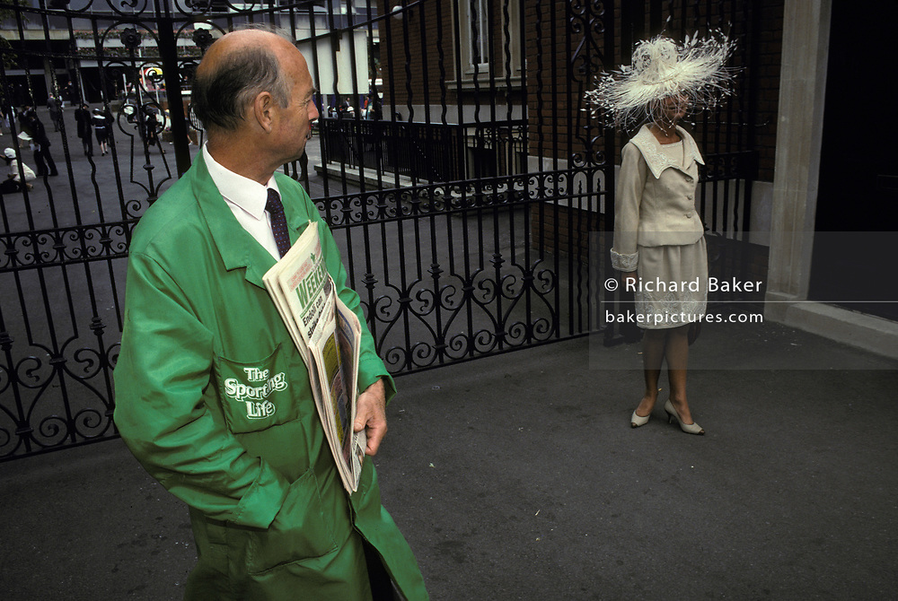 A Racing Post vendor looks over to a young woman wearing a wide-brimmed hat on Ladies' Day during Royal Ascot, the annual event on the English sporting and social calendar, on 18th June 1992, in London, England. Royal Ascot is held every June and is one of the main dates on the sporting calendar and English social season. Over 300,000 people make the annual visit to Berkshire during Royal Ascot week, making this Europe's best-attended race meeting. There are sixteen group races on offer, with at least one Group One event on each of the five days. The Gold Cup is on Ladies' Day on the Thursday. There is over £3 million of prize money on offer.