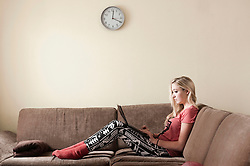 Teenage girl with laptop siiting on couch