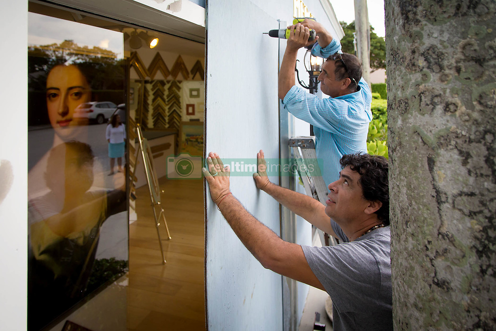 September 5, 2017 - Palm Beach, Florida, U.S. - GIBERTO COUTREAS (foreground) and LUIS PACHECO board up a frame shop in preparation for hurricane Irma at the House of Kahn on Peruvian Avenue in Palm Beach. (Credit Image: © Allen Eyestone/The Palm Beach Post via ZUMA Wire)