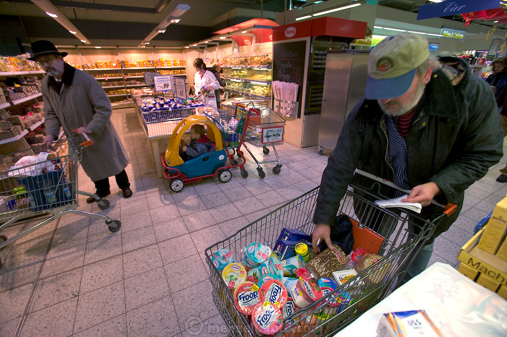 Jörg Melander (at right), shops at the Famila supermarket. (Supporting image from the project Hungry Planet: What the World Eats.) The Melander family of Bargteheide, Germany, is one of the thirty families featured, with a weeks' worth of food, in the book Hungry Planet: What the World Eats.