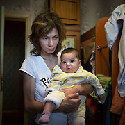 CAPTION: Oksana is mother to four children, including five-month-old Ksenya. Together, they live in a space measuring just 4m by 4m. Partnership For Every Child (P4EC) has at times supported Oksana with emergency interventions. For example, when Ksenya was born, P4EC arranged for her two elder daughters to stay with a foster family, while her son stayed at a hospital. NAMES MUST BE CHANGED. LOCATION: St Petersburg, Russia. INDIVIDUAL(S) PHOTOGRAPHED: Oksana Orlova (mother) and Klara Orlova (baby).