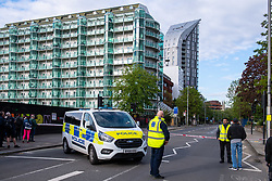© Licensed to London News Pictures. 25/05/2021. London, UK. A police van blocks traffic on Uxbridge Road in Ealing after a large section of cladding on the Arc Tower (right) came loose. The road remained closed while the building was made safe. Photo credit: Peter Manning/LNP