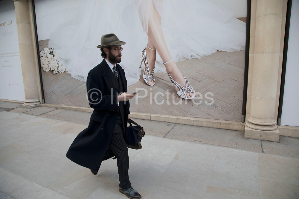 Well dressed man in a pin striped suit, winter coat and hat passes a hoarding on Bond Street showing some expensive shoes encrusted with jewels in this most exclusive of shopping streets in London, England, United Kingdom.