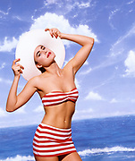 Happy woman in straw hat and striped bathing suit in front of sky background