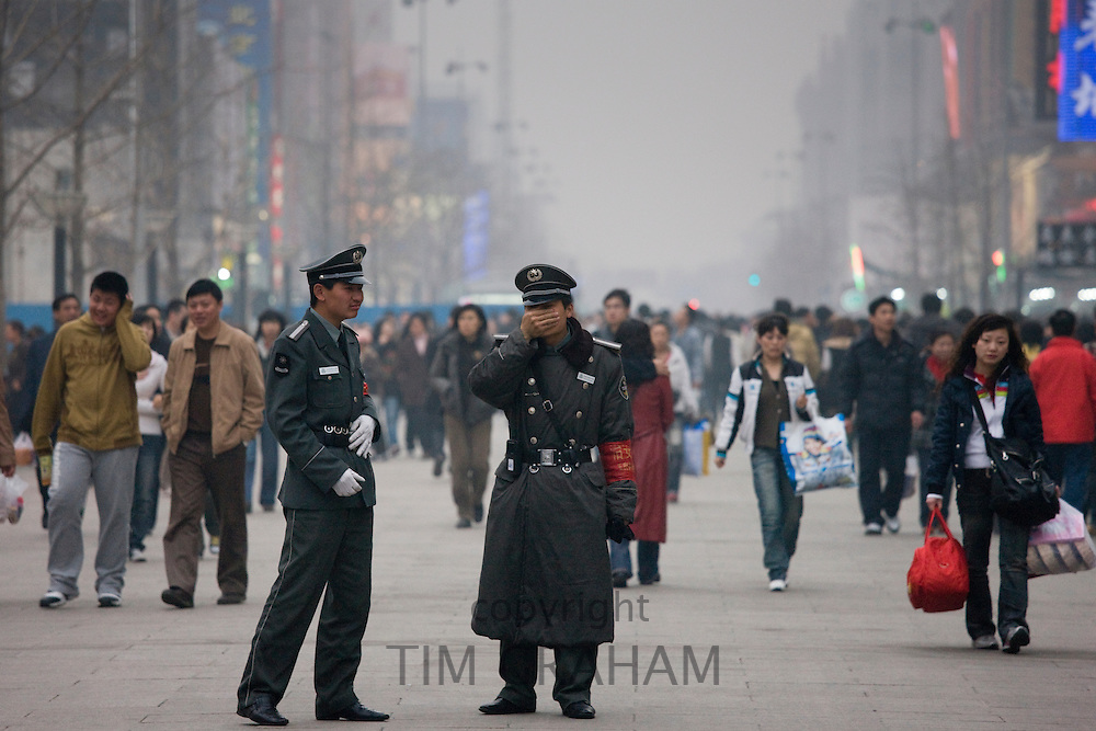 Chinese policemen on Wangfujing street of Central Beijing, China