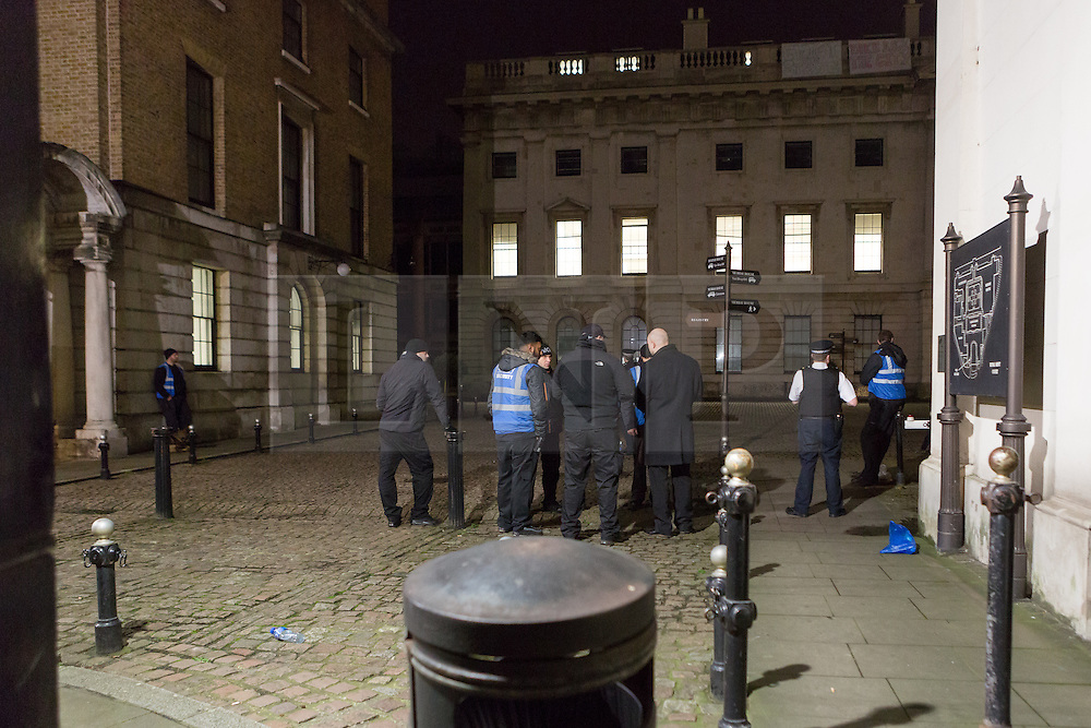 © Licensed to London News Pictures. 29/12/2015. London, UK. Security staff and police inside the grounds of the Royal Mint building. Squatters have occupied the Royal Mint building, located opposite the Tower of London on the border of the City of London to protest against homelessness and highlight how empty buildings could provide shelter for rough sleepers. The site was previously used to manufacture British coins but is currently vacant and activists argue that this along with other vacant commercial buildings could be used to provide short term shelter for the homeless. Photo credit : Vickie Flores/LNP