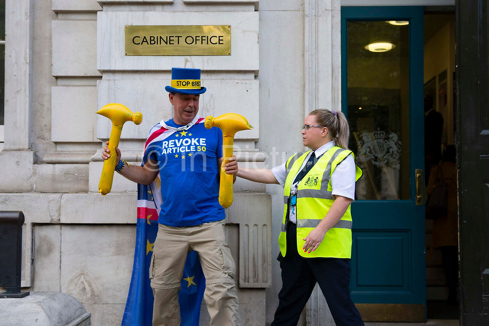 A security guard removes pro remain campaigner Steve Bray holding two rubber yellow hammers outside the Cabinet Office in London, United Kingdom on 12th September 2019. Last night the government published details of Operation Yellowhammer which is the codename used by the UK Treasury for cross-government civil contingency planning fin the event of a no-deal Brexit after MPs voted to force its release.