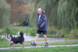 ©Licensed to London News Pictures 08/10/2020  <br /> Sidcup, UK. A man walking his dog wearing shorts and a smile. Cold and wet autumn weather this morning at Footscray Meadows in Sidcup, South East London. Photo credit:Grant Falvey/LNP