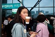 Junge Dame mit Kaffee und Mobil Telefon am Express Bus Terminal im Zentrum der koreanischen Hauptstadt Seoul. <br /> <br /> Young woman with coffee and mobil phone at the Express Bus Terminal in the city center of the Korean capital Seoul.