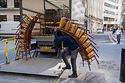 Contractors with the hospitality furniture supplier 'Well Dressed Tables', load tall stacks of event chairs into the company lorry after a function at Lloyds of London in the City of London, the capital's financial district, on 24th September 2021, in London, England.