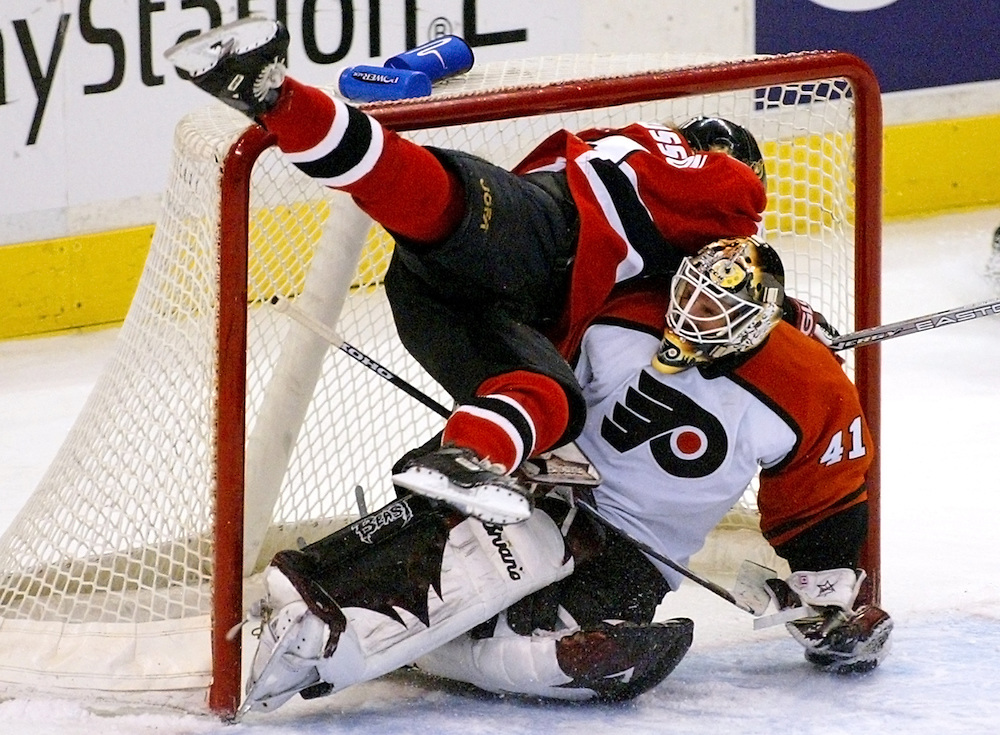 Ottawa Senators' Daniel Alfredsson crashes into Philadelphia Flyers' goalie Sean Burke (41) during NHL action in Ottawa, February 26, 2004. No penalty was called on the play and the game ended in a 1-1 tie. REUTERS/Jim Young