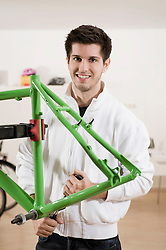 Young man working on bicycle frame, smiling, portrait