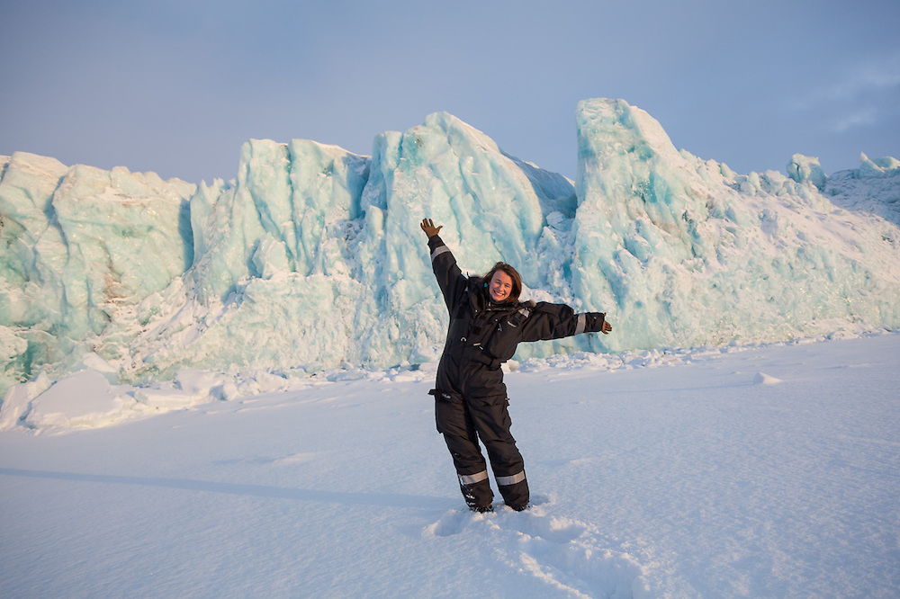 UNIS student Kiya Riverman poses on sea ice in front of the tidewater terminus of Tunabreen, Svalbard.