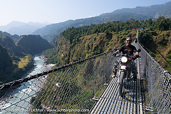 Round the World Doug Wothke riding across the Kushma - Gyadi suspension bridge over the Modi River (the highest, at 384 feet, and longest, at 1,128 feet, suspension bridge in Nepal) during Motorcycle Sherpa's Ride to the Heavens motorcycle adventure in the Himalayas of Nepal. On the sixth day of riding, we went from Tatopani to Pokhara. Saturday, November 9, 2019. Photography ©2019 Michael Lichter.