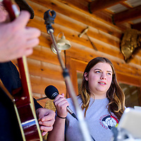 Hannah Lind takes the mic as she prepares to sing along with Wayne Ramm at the Candy Kitchen Trading Post during a winter solstice celebration in Candy Kitchen Saturday.