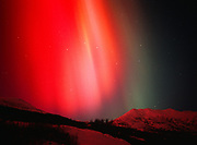View looking north of red and green aurora casting light on snow of the Talkeetna Mountains, geomagnetic storm on the evening of November 5, 2001, Little Susitna River Valley, Alaska.