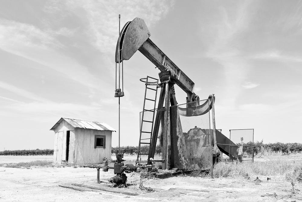 USA, Kalifornien, Eine Blechhütte steht neben einer Ölförderpumpe inmitten eines Feldes |USA, California, A sheet metal hut standing next to an oil pump in the middle of a field