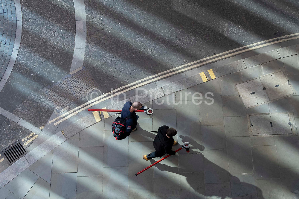 While office workers remain at home in accordance to government Covid guidelines and individual corporate policies, two contractors carry their tools through reflected light in the street  in the City of London, the capitals financial district, during the third lockdown of the Coronavirus pandemic, on 9th March 2021, in London, England.