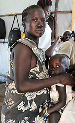 A woman at Kulubi reception centre waits for her child to be medically screened before being taken to BidiBidi settlement camp.