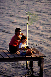 Stock photo of a woman with a young boy fishing from a wooden pier