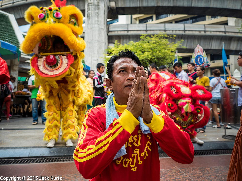 """04 SEPTEMBER 2015 - BANGKOK, THAILAND: Chinese lion dancers perform in a special merit making ceremony at the Erawan Shrine Friday. A """"Holy Religious Ceremony for Wellness and Prosperity of our Nation and Thai People"""" was held Friday morning at Erawan Shrine. The ceremony was to regain confidence of the Thai people and foreign visitors, to preserve Thai religious customs and traditions and to promote peace and happiness inThailand. Repairs to Erawan Shrine were completed Thursday, Sept 3 after the shrine was bombed on August 17. Twenty people were killed in the bombing and more than 100 injured. The statue of the Four Faced Brahma in the shrine was damaged by shrapnel and a building at the shrine was damaged by debris.     PHOTO BY JACK KURTZ"""