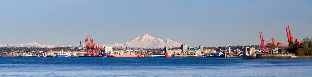 Mount Baker behind Port Metro Vancouver.  Photographed from the Stanley Park seawall near the Lions Gate Bridge in Vancouver, British Columbia, Canada