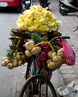 The bicycle of a street vendor overflows with produce in the old quarter of Hanoi.