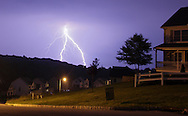 Middletown, New York - Lightning strikes in the distance behind homes in a development  on during a thunderstorm on the night of Saturday, June 12, 2010.