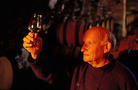 Wine maker Rene Dauvissat observing the color of a glass of Chablis taken from his oak barrels in his cellar - Chablis, Burgundy.  Dauvissat's Chablis are considered among the best.