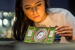 """© Licensed to London News Pictures. 31/05/2019. LONDON, UK. A staff member views """"A rare Fabergé silver-gilt enamel and seed pearl triptych clock and frame"""" by workmaster Johan Victor Aarne, 1880-1904 (Est. GBP 150,000-200,000) at a preview of works from the upcoming sale of Russian Pictures, Works of Art, Fabergé & Icons Sales at Sotheby's, New Bond Street, on 4 June 2019.  Photo credit: Stephen Chung/LNP"""