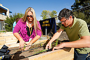 Milpitas High School assistant principal Hilary Brittan and special education teacher Mark Mullins plant onions during a special event showcasing the American Heart Association Teaching Garden at Milpitas High School in Milpitas, California, on October 8, 2013. (Stan Olszewski/SOSKIphoto)