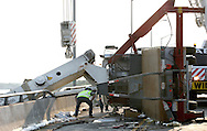 A worker inspects a crane truck before trying to use another larger crane to lift it off the Route 90 bridge in Ocean City. The truck crashed on the bridge late Thursday afternoon, ending up on its side with its crane hanging over the edge almost in the waters of the Assawoman Bay..