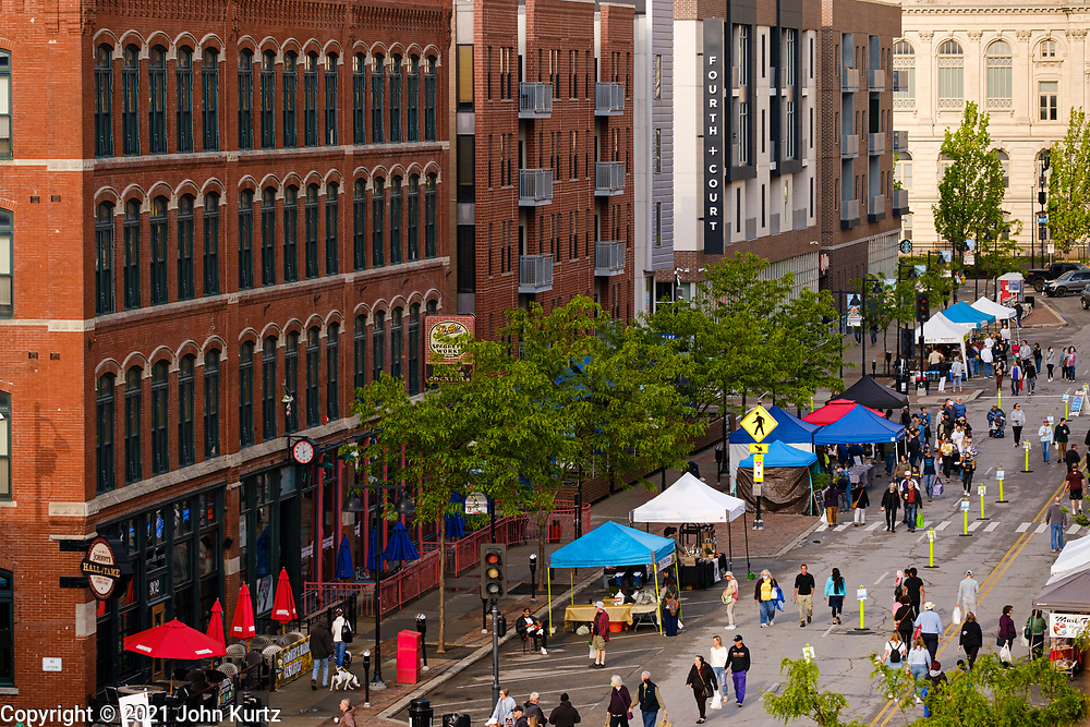 15 MAY 2021 - DES MOINES, IOWA: People walk through the Des Moines Farmers Market. The Des Moines Farmers Market is the largest weekly Farmers Market in Iowa. The market was largely cancelled in 2020 because of COVID-19 pandemic, but reopened in a limited way in 2021. In order to comply with Coronavirus safety guidelines, traffic is one way past the stands and people are required to wear face masks. Traditionally about 25,000 people attended the Saturday morning market, and about 40,000 people attended market on the opening day, the first Saturday in May. This year there will be about 115 vendors, 75% the normal number of vendors. As the CDC rolls back Coronavirus guidelines, the market is expanding. The market will expand Memorial Day weekend to include prepared food stands and children's activities.          PHOTO BY JACK KURTZ